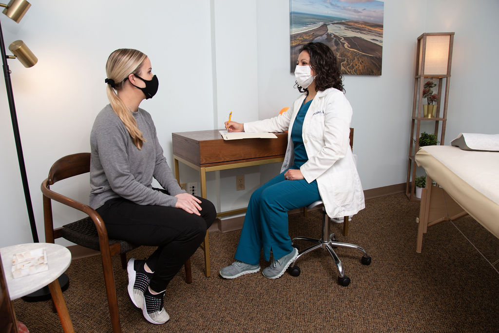 Montserrat Gonzales doing a consultation with a client, both in masks