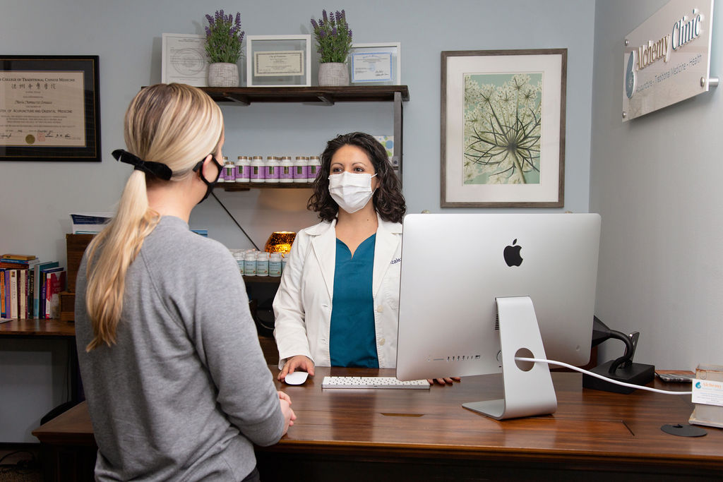 Montserrat Gonzales in a mask assisting a patient at the front desk of Alchemy Clinic